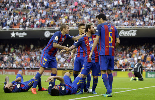 FC Barcelona's Lionel Messi, second right, argues with the crowd after they threw objects, after scoring a penalty during the Spanish La Liga soccer match between Valencia and FC Barcelona at the Mestalla stadium in Valencia, Spain, Saturday, Oct. 22, 2016. (AP Photo/Manu Fernandez)