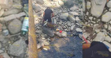 Captan a una persona enjuagando botes de químicos en el río Necaxa